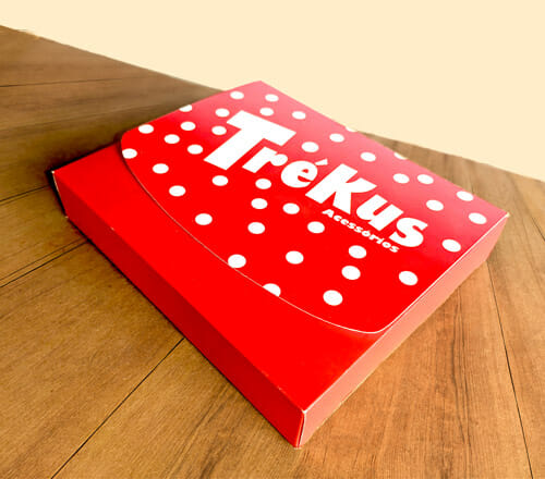 """Caixa maleta com janela personalizada, está fechada e é personalizada na cor vermelha , com a tampa com detalhes em bolinhas brancas escrito """"Trékus Acessórios""""."""