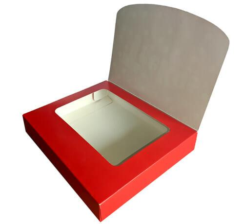 Caixa maleta com janela personalizada com a tampa aberta, é possível ver uma segunda tampa, vermelha com uma janela que dá para o interior da caixa. A embalagem está ligeiramente rotacionada para a esquerda.