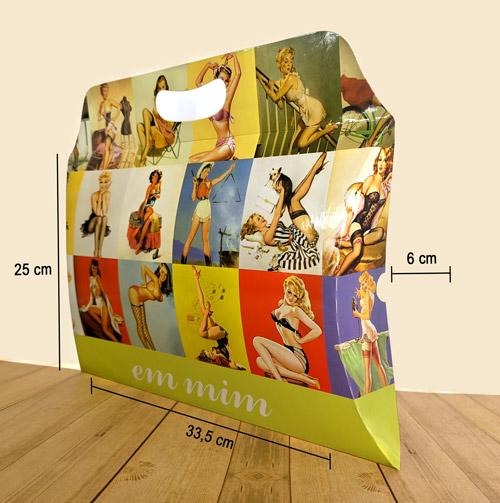 """Caixa travesseiro grande com alça personalizada da marca """"Em Mim"""", na parte inferior da embalagem tem uma faixa verde e tem escrito o nome da marca em fonte cursiva, e no resto da embalagem é cheio de imagens de mulheres pin-ups. Tem três linhas que indicam as dimensões da embalagem, sendo respectivamente: Largura 33,5cm - altura 25cm - largura 6cm. A embalagem está sobre uma mesa de madeira."""
