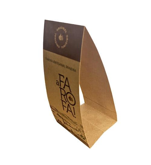 """Envoltório de embalagem personalizado com a marca """"A Farofa!"""", o envoltório é feito no papel kraft, tem duas faixas marrons, na parte superior a faixa é mais grossa, tem o desenho de uma cebola e é escrito """"original"""", a faixa marrom na parte de baixo é escrito o peso do produto (300g), no meio, pouco abaixo da faixa marrom é escrito """"Farofa Artesanal Mineira"""" e logo abaixo vem o logotipo """"A FAROFA!"""" e abaixo do logo tem o desenho da Serra da Canastra. O envoltório está ligeiramente virado para a esquerda."""