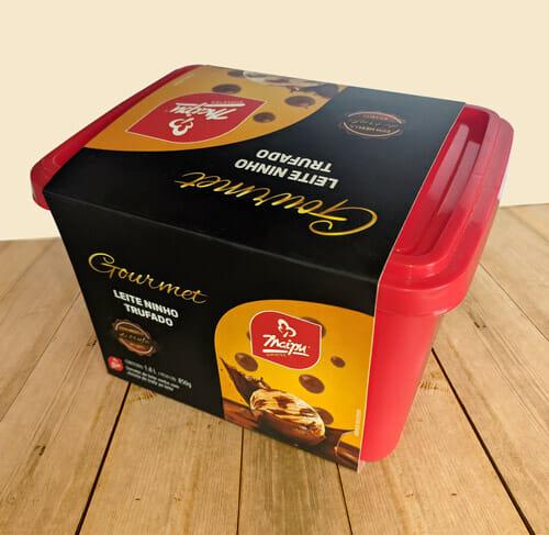"""Envoltório de sorvete personalizado da Empresa Maipu, o envoltório é preto, escrito """"Gourmet"""" em dourado, e abaixo do gourmet o sabor do sorvete que é """"leite ninho trufado"""", tem um retângulo arrendondado no canto inferior direito, com o logotipo da Maipu, e abaixo uma bola de sorvete amarela com gotas de chocolate, a bola está caindo dentro de uma calda de chocolate, que está esparramando para cima, na parte superior também tem a mesma foto. A embalagem de sorvete rodeada com o envoltório está sobre uma mesa de madeira."""