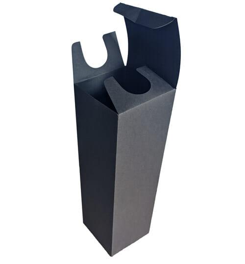 Caixa personalizada de bebida em papel preto, ela foi fotografada ligeiramente de cima e está aberta, sendo possível ver duas orelhas com um recorte redondo e a tampa aberta.