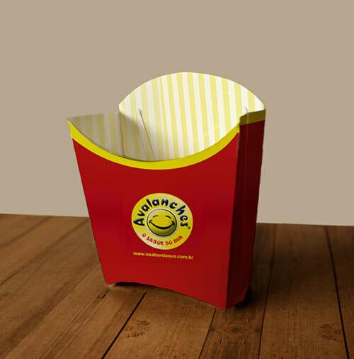 Caixa de batata fritas na cor vermelha, com detalhes em amarelo, com o logotipo do Avalaches, que é uma carinha sorridente com o nome em curva logo acima. A embalagem está em cima de uma mesa de madeira.