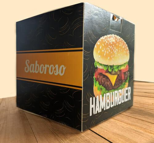 """caixa Hamburguer Personalizada, a cor predominante é preta, com uma textura de hambúrgueres desenhados em amarelo. Na face a esquerda é possível ver uma tira em amarela com o escrito """"saboroso"""" em branco e na face a direita uma foto de um lanche com a palavra """"hambúrguer"""" abaixo. A caixa está sobre uma mesa de madeira."""