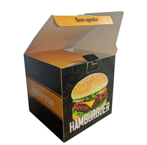 """caixa Hamburguer Personalizada, a cor predominante é preta, com uma textura de hambúrgueres desenhados em amarelo. Na face a esquerda é possível ver uma tira em amarela com o escrito """"saboroso"""" em branco e na face a direita uma foto de um lanche com a palavra """"hambúrguer"""" abaixo, é possível ver que a caixa está aberta, as orelhas da caixa são amarelas e na lingueta da tampa é escrito """"bom apetite!"""" na cor preta."""