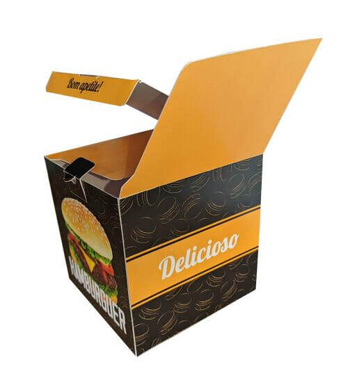 """caixa Hamburguer Personalizada, a cor predominante é preta, com uma textura de hambúrgueres desenhados em amarelo. Na face a esquerda é possível ver uma foto de um lanche com a palavra """"hambúrguer"""" abaixo, e na face direita é possível ver uma faixa amarela escrito """"delicioso"""", é possível ver que a caixa está aberta, as orelhas da caixa são amarelas e na lingueta da tampa é escrito """"bom apetite!"""" na cor preta."""