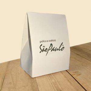 Caixa para acessórios personalizada triangular, possui o logo da Gráfica São Paulo na frente em hotstamping prata. A caixa está sobre uma mesa de madeira.