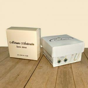 """Duas caixas de acessórios personalizadas, quadradas, a da esquerda é bege e está escrito """"Miriam Andrade Semi Jóias"""" e a segunda caixa é branca com a imagem de dois brincos de pedra azul e um anel ao lado. Também dá pra ver um pouco da tampa da embalagem a direita e é possível ler """"Exclusiva semi jóias"""". Ambas as embalagens estão sobre uma mesa."""