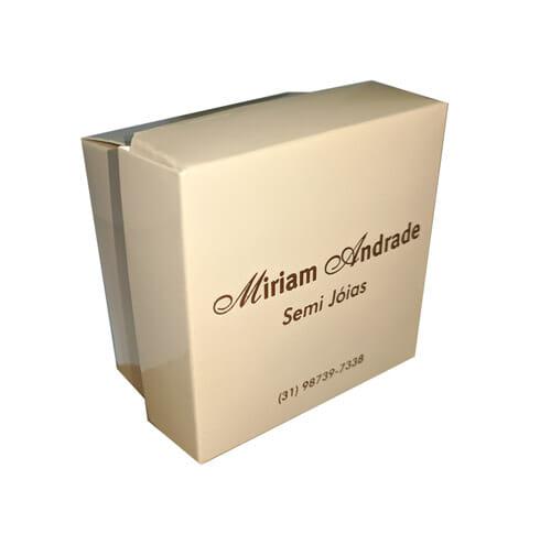 """Caixa de acessórios quadrada na cor bege, a caixa está virada em torno de 45 graus e é possível ver o logotipo """"Miriam Andrade Semi Jóias""""."""