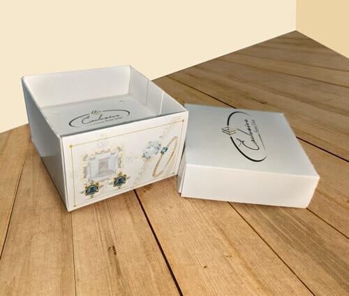 """Caixa acessórios com tampa e suporte personalizada da empresa """"Exclusiva Semi Jóias"""", a embalagem é branca com detalhes de jóias nas laterais, a tampa está colocada ao lado da embalagem então é possível ver o suporte para acessórios dentro da caixinha. A embalagem está sobre uma mesa de madeira."""