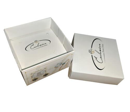 """Caixa acessórios com tampa e suporte personalizada da empresa """"Exclusiva Semi Jóias"""", a embalagem é branca com detalhes de jóias nas laterais, a tampa está colocada ao lado da embalagem então é possível ver o suporte para acessórios dentro da caixinha."""