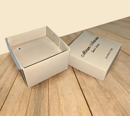 """Caixa acessórios com tampa e suporte personalizada da empresa """"Miriam Semi Jóias"""", a embalagem é bege, a tampa está colocada ao lado da embalagem então é possível ver o suporte para acessórios dentro da caixinha. A embalagem está sobre uma mesa de madeira."""