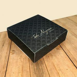 """Caixa para acessórios quadrada personalizada da empresa """"Tati Negrão Semijoias"""", a caixa é cor de chumbo com arabescos em preto e está sobre uma mesa de madeira."""