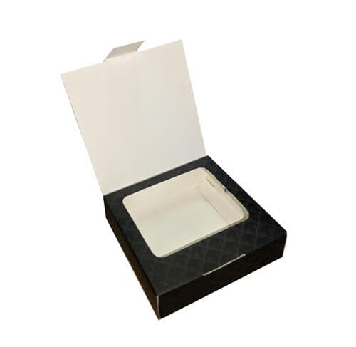 """Caixa para acessórios quadrada personalizada da empresa """"Tati Negrão Semijoias"""", a caixa é cor de chumbo com arabescos em preto, a tampa da caixa está aberta, revelando um suporte parecido com uma janela dentro da caixa, sendo possível ver a parte interna dela."""