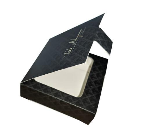 """Caixa para acessórios quadrada personalizada da empresa """"Tati Negrão Semijoias"""", a caixa é cor de chumbo com arabescos em preto, a tampa da caixa está semi-aberta, revelando um suporte parecido com uma janela dentro da caixa, sendo possível ver um pedaço da parte interna dela."""