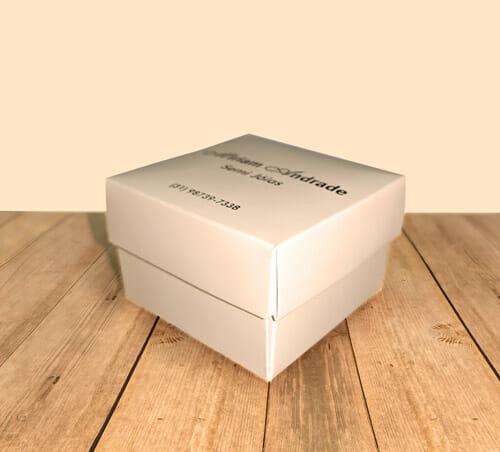 """Caixa para acessórios personalizada, quadrada, na cor bege, com a tampa com o logotipo da """"Miriam Andrade Semi Jóias"""". A embalagem está sobre uma mesa de madeira."""
