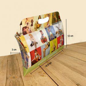 """Caixa travesseiro pequena com alça personalizada da empresa """"Em Mim"""", em uma faixa verde na parte de baixo da embalagem. A embalagem é decorada com várias fotos de mulheres pin-up. Tem três linhas representando respectivamente: comprimento 23cm, largura 3,5cm e altura 15cm. A embalagem está sobre uma mesa de madeira."""