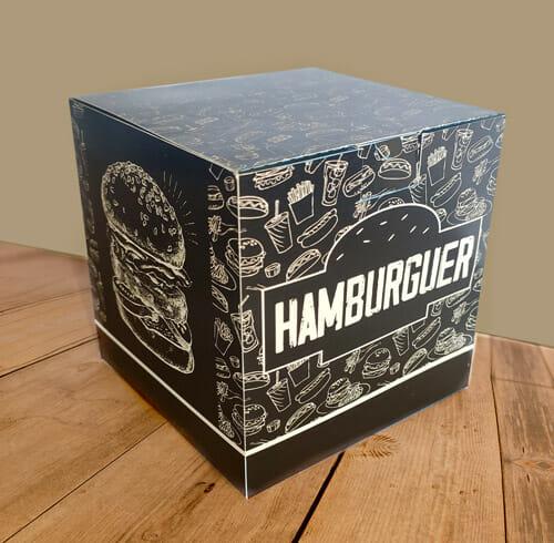 """Caixa hambúrguer personalizada na cor preta, com uma textura de fundo branca com vários desenhos de sanduíches, cachorro-quentes, refrigerantes e batatas. É possível ver duas faces da embalagem, sendo a face esquerda com o desenho de um sanduíche grande, sobre fundo preto e na lateral direita, a palavra """"hambúrguer"""" dentro da silhueta de um hambúrguer."""