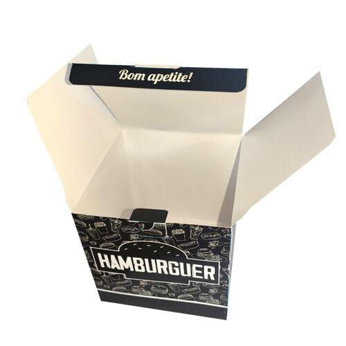 """Caixa hambúrguer personalizada na cor preta, com uma textura de fundo branca com vários desenhos de sanduíches, cachorro-quentes, refrigerantes e batatas. Na parte da frente é possível ver palavra """"hambúrguer"""" dentro da silhueta de um hambúrguer. A embalagem está aberta e na lingueta que fecha a caixa está escrito """"Bom apetite""""."""