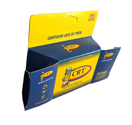 """Caixa com suporte para gôndola personalizada pequena, a caixa é predominantemente amarela e tem escrito em azul escuro no suporte para gôndola """"100% testado e garantido"""" e mais abaixo """"cartucho jato de tinta"""", a caixa tem um degradê de azul escuro para o amarelo, no centro da caixa tem um mascote da marca CRT Cartuchos que é um cartucho de tinta de allstar vermelho, luva verde e com um grande par de olhos. A foto foi tirada de cima e do lado esquerdo, e é possível ver a lateral de superior com o logotipo e mascote da CRT. A lateral esquerda tem o logotipo e o mascote com três símbolos, de """"reciclagem"""", """"não molhar"""", e """"este lado para cima"""". O lado direito está aberto também e é possível ver o logotipo e o mascote da CRT com três números de telefone abaixo dele."""