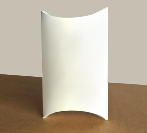 Micro caixa travesseiro personalizada na cor branca sem impressão, ela está virada de frente e está sobre uma mesa de madeira.