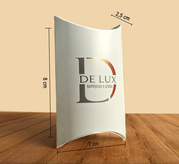 """A caixa travesseiro micro está personalizada com o logotipo da empresa """"De Lux semijoias e pratas"""", a embalagem é branca e está em pé sobre uma mesa de madeira. Na imagem é possível ver três linhas mostrando as dimensões da embalagem, que são respectivamente: comprimento 7cm, largura 2,5cm, altura 8cm."""