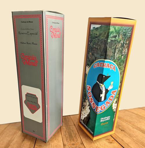 """Caixa Personalizada para Bebida, são duas caixas sobre uma mesa de madeira, a caixa da esquerda é prateada com detalhes em vermelho nas duas faces visíveis e é da marca """"Coração de Minas"""", a da direita é da marca """"Cachaça Sossegada"""", e a embalagem é amarela com detalhes em marrom, com uma foto de um cânion ao fundo."""