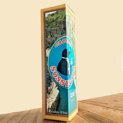 """Caixa de bebida personalizada da """"Cachaça Sossegada"""", atrás do logotipo tem uma foto de um cânion com água bem azul, ao redor da imagem tem uma borda marrom e amarela. A caixa está sobre uma mesa de madeira."""