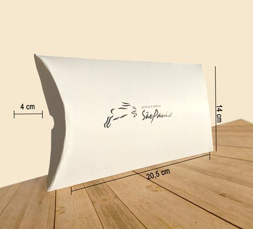 Caixa travesseiro personalizada média na cor branca com o logotipo da Gráfica e Editora São Paulo, com o logotipo em hotstamping da Gráfica e Editora São Paulo. Três linhas mostram a área útil da embalagem, respectivamente: comprimento 20,3cm - largura 4cm - altura 14cm. A embalagem encontra-se em cima de uma mesa de madeira.