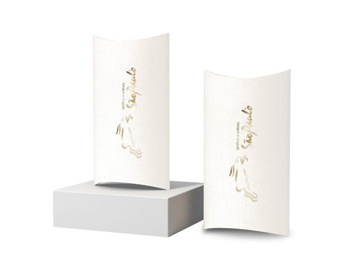 Duas caixas travesseiro, a da esquerda está apoiada sobre uma caixinha cinza, as duas possuem o logotipo da gráfica são paulo em hotstamping dourado.