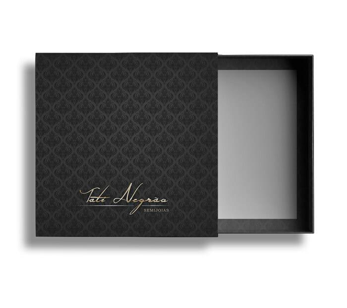 Uma caixa quadrada, com uma gaveta saindo, a gaveta está metade aberta e a caixa principal é cinza chumbo com arabescos em preto. Na parte de baixo tem o logotipo dourado escrito a mão chamado Tati Negrão Semijoias.