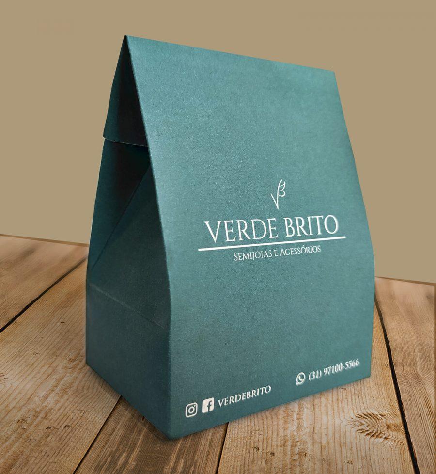 """Caixa Triangular Personalizada na cor verde escrito """"verde brito"""". A embalagem está sobre uma mesa de madeira com fundo bege."""