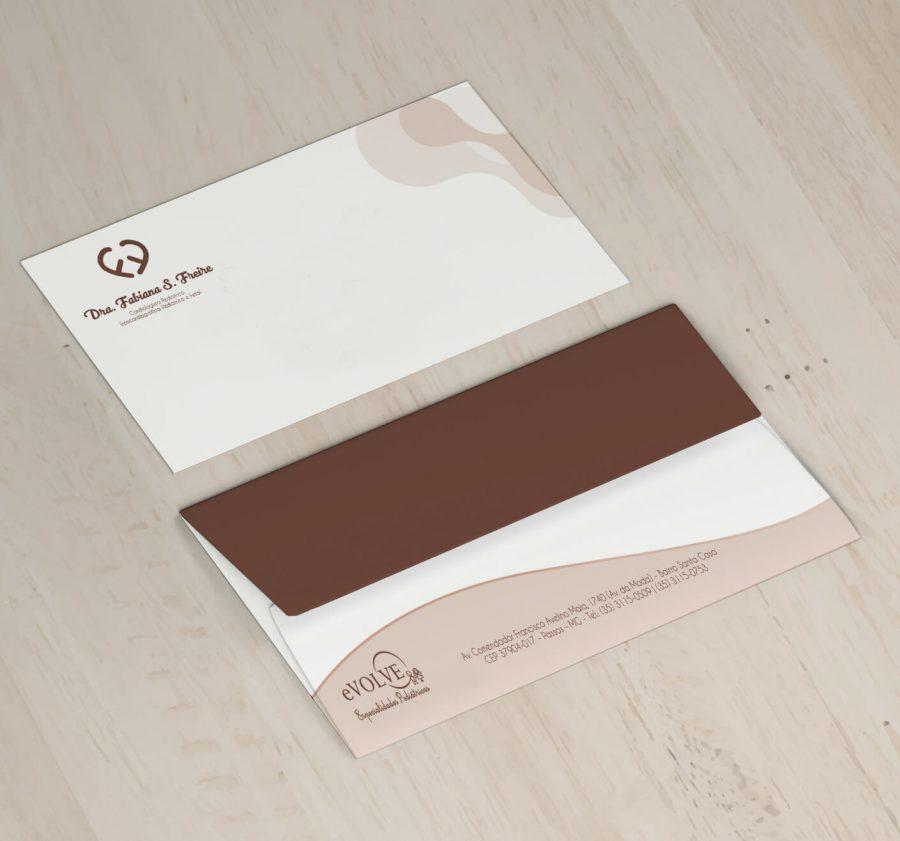 Dois envelopes representando a frente e verso, em detalhes marrom escuro e claro, sobre uma mesa de madeira
