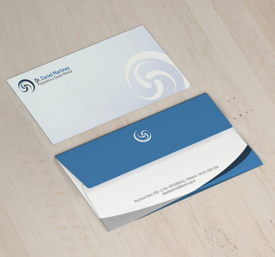 Dois envelopes representando frente e verso com detalhe azul e azul claro sobre uma mesa de madeira