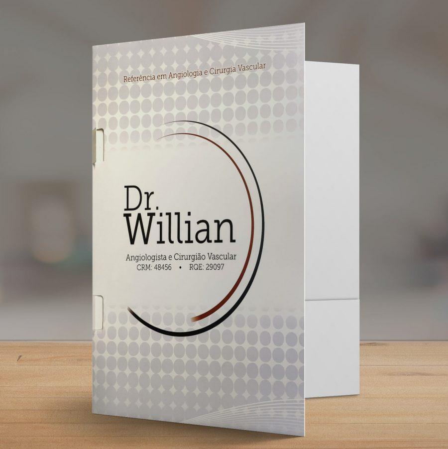 """Pasta de consultório com uma dobra na cor branca com detalhes cinza com a logo """"dr willian"""" ao centro, fundo cinza na mesa madeira"""