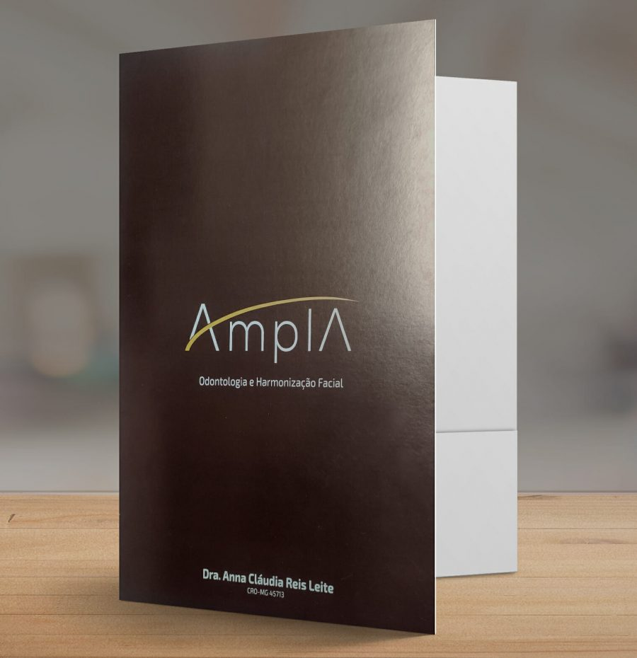 """Pasta personalizada em duas cores, a pasta é marrom escuro com o logo """"Amplia"""" na frente. A pasta está aberta sobre uma mesa de madeira."""