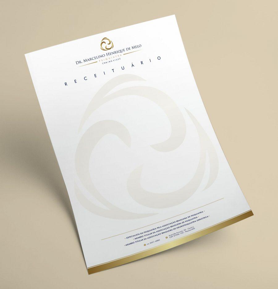 Receituário branco com detalhes em dourado na base com uma logomarca grande em marca dágua sobre um fundo bege